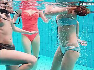 three nude dolls have fun underwater