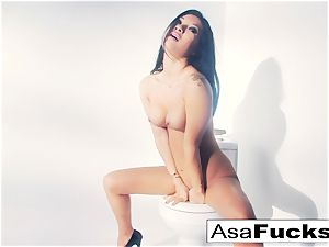 Asa Akira uses a faux arm to satisfy her pussy