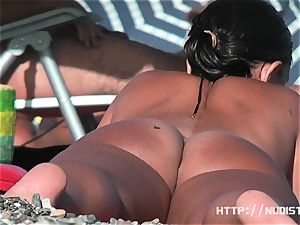 Playful girls demonstrate their mounds in the bare beach